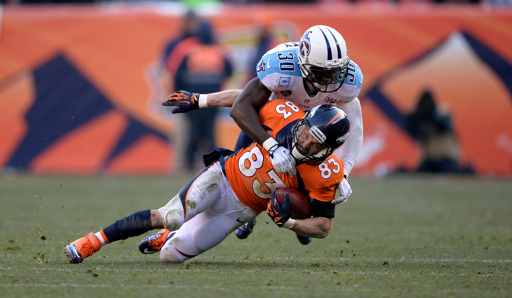 . DENVER, CO - DECEMBER 8: Denver Broncos wide receiver Wes Welker (83) gets wrapped up and taken down by Tennessee Titans cornerback Jason McCourty (30) during the first half.  The Denver Broncos vs. the Tennessee Titans at Sports Authority Field at Mile High in Denver on December 8, 2013. (Photo by Hyoung Chang/The Denver Post)