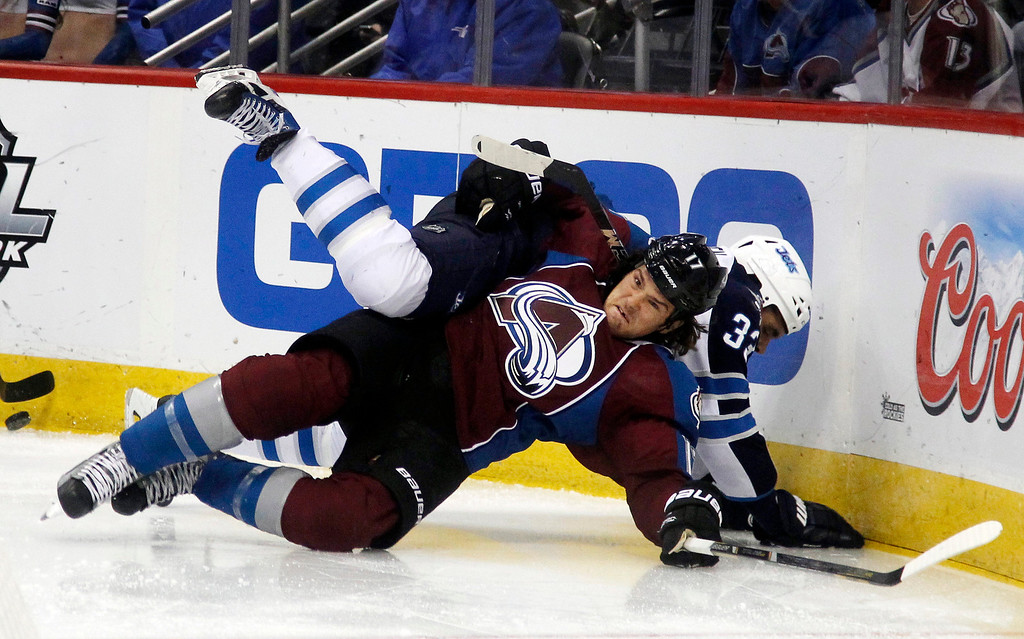 . Colorado Avalanche right wing Steve Downie, front, gets tangled up with Winnipeg Jets defenseman Dustin Byfuglien while fighting for control of the puck in the second period of an NHL hockey game in Denver on Sunday, Oct. 27, 2013. (AP Photo/David Zalubowski)
