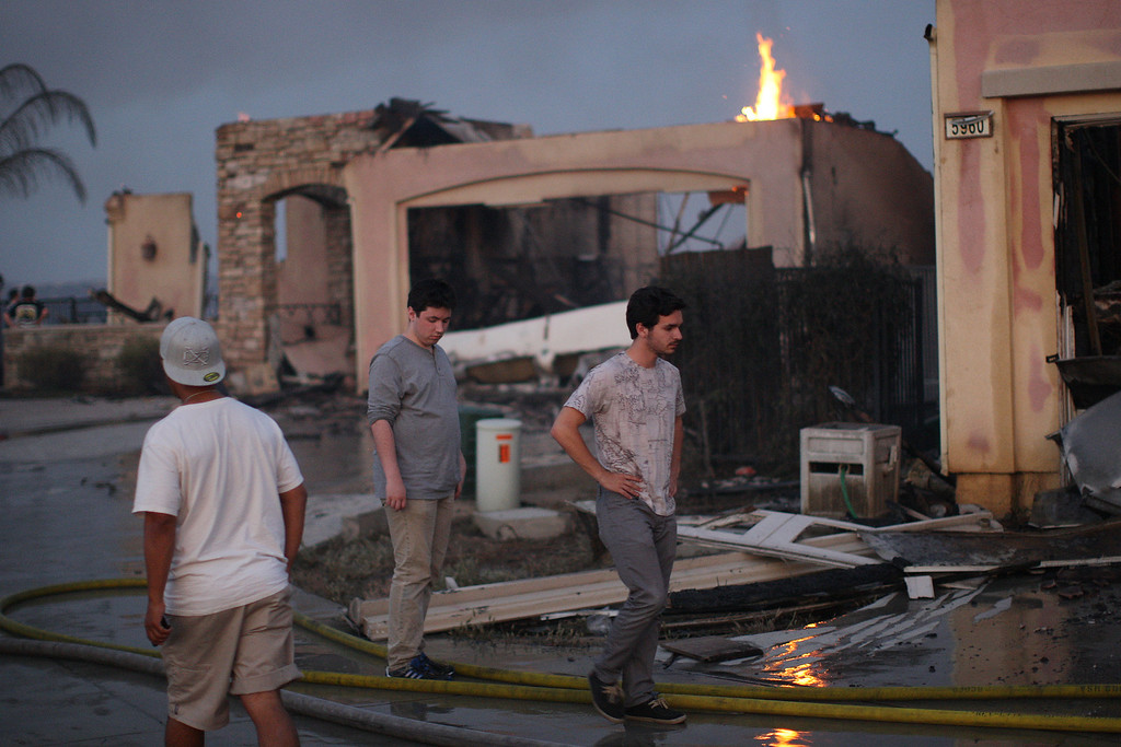 . Residents looks at the burning remains of their home that was destroyed in the Poinsettia fire, one of nine wildfires fueled by wind and record temperatures that erupted in San Diego County throughout the day, on May 14, 2014 in Carlsbad, California.(Photo by David McNew/Getty Images)