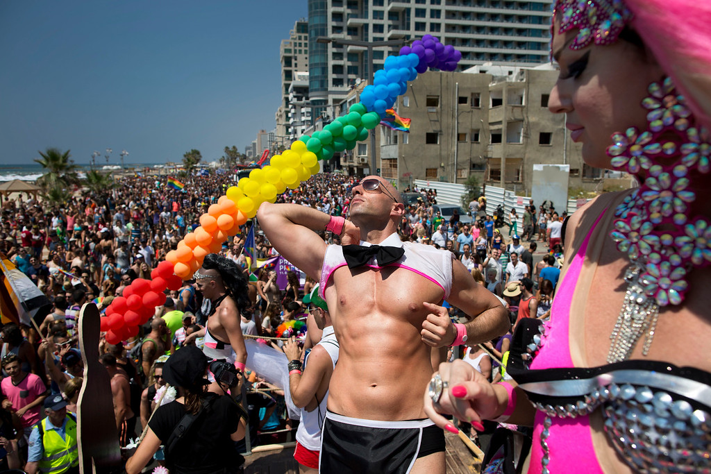 . Israeli dancers perform during the annual Gay Pride Parade on a street of Tel Aviv, Israel, Friday, June 13, 2014. Shirtless Israeli men, colorfully dressed drag queens and others partied Friday through central Tel Aviv as it celebrates the week-long event that supports lesbian, gay, bisexual and transgender people and their supporters, also known as the LGBT community. (AP Photo/Oded Balilty)