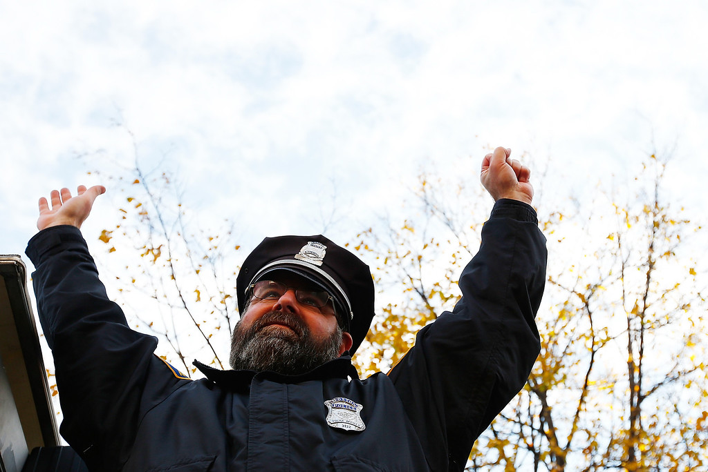 . BOSTON, MA - NOVEMBER 02: Boston Police officer, Steve Horgan, raises his arms during the World Series victory parade on November 2, 2013 in Boston, Massachusetts.  (Photo by Jared Wickerham/Getty Images)