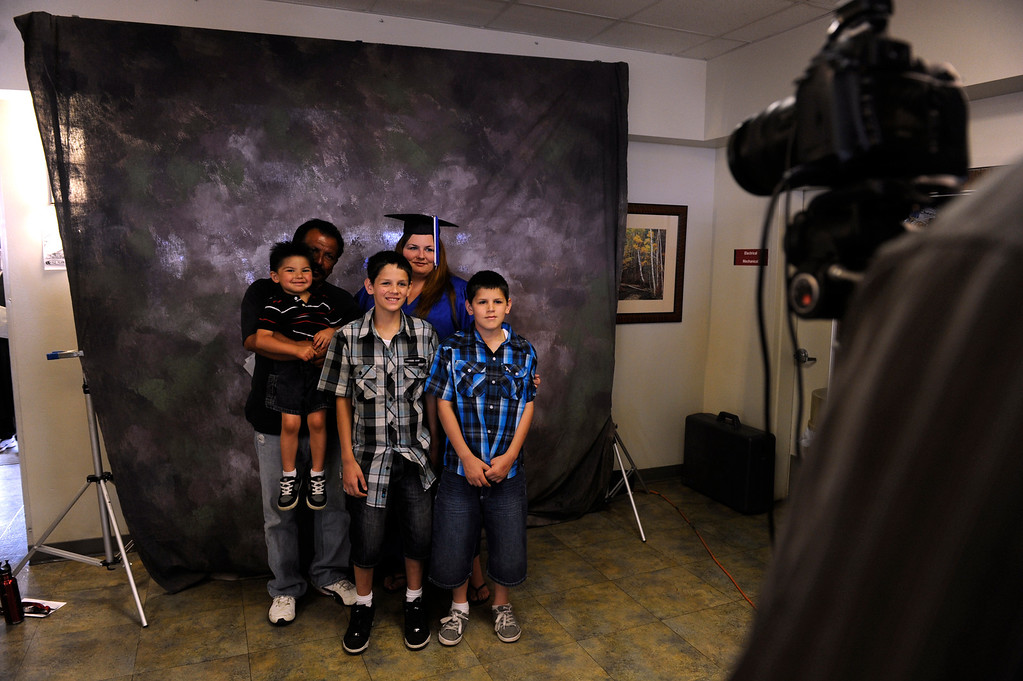 . Graduate Kandie Gonzales has her photo taken with her husband Tony holding son Ezekiel, 3, along with Anthony, 11, right, and Joseph, 10. (Photo By Kathryn Scott Osler/The Denver Post)