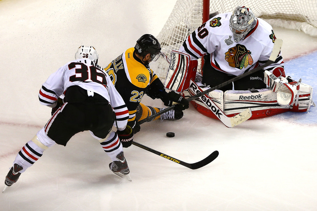 . Corey Crawford #50 of the Chicago Blackhawks stops a shot by Chris Kelly #23 of the Boston Bruins in Game Three of the 2013 NHL Stanley Cup Final at TD Garden on June 17, 2013 in Boston, Massachusetts.  (Photo by Elsa/Getty Images)