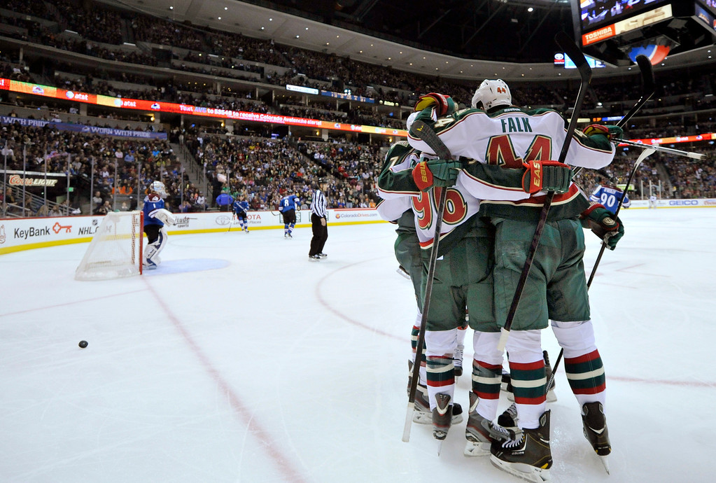 . Members of the Minnesota Wild celebrate a goal by Pierre-Marc Bouchard (96)  during the second period of an NHL hockey game against the Colorado Avalanche on Saturday, March 16, 2013, in Denver. (AP Photo/Jack Dempsey)