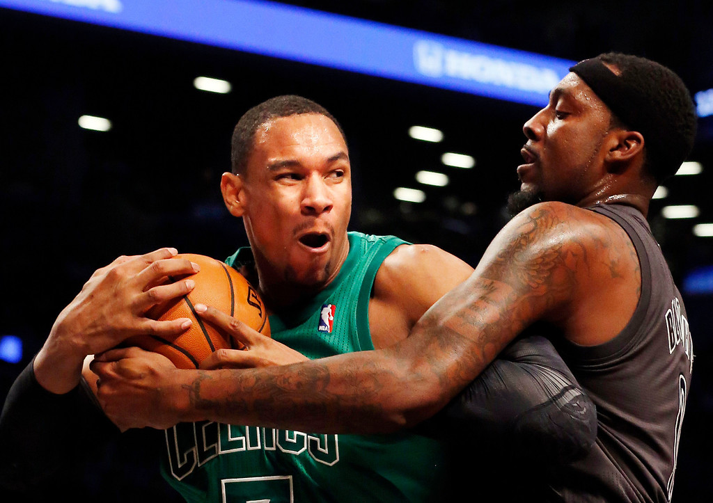 . Boston Celtics forward Jared Sullinger (7) and Brooklyn Nets forward-center Andray Blatche (0) battle for the ball in the first half of their NBA basketball game at the Barclays Center, Tuesday, Dec. 25, 2012, in New York. (AP Photo/John Minchillo)