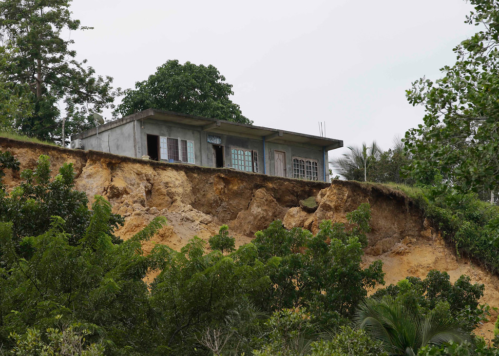 . A house is perched precariously amidst a landslide caused by a 7.2-magnitude earthquake at Cortes township, Bohol province in central Philippines Wednesday Oct. 16, 2013. (AP Photo/Bullit Marquez)