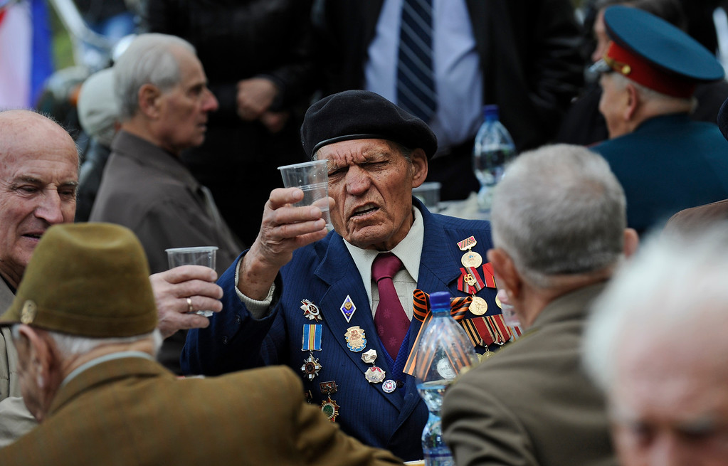 . A WWII veteran toasts during a celebration of the 70th anniversary of the liberation of Simferopol, Crimea, Sunday, April 13, 2014. On Sunday, residents of Simferopol mark the 70th anniversary of liberation of Simferopol from German troops during World War II. (AP Photo/ Andrew Lubimov)