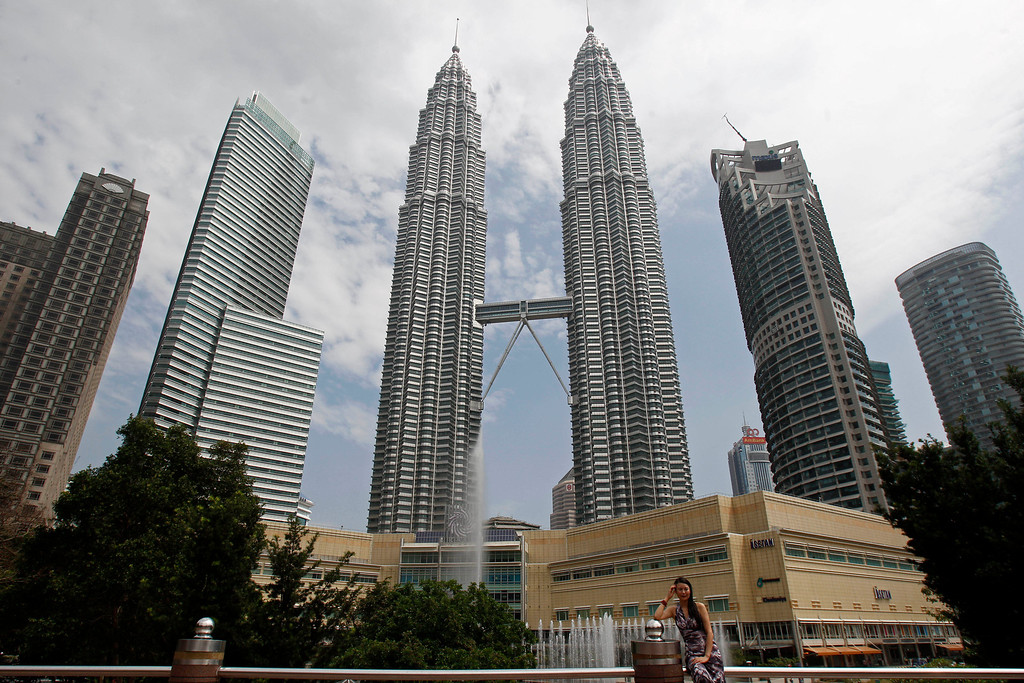 . In this June 27, 2013 file photo, a tourist poses for a photo in front of Malaysia\'s landmark Petronas Twin Towers in Kuala Lumpur, Malaysia. According to the nonprofit Council on Tall Buildings and Urban Habitat, the Petronas 1 and 2 Towers will be the seventh and eighth tallest completed buildings in the world, with a height measured at 1,483 feet, once New York\'s 1 World Trade Center, with a height of 1,776 feet, is completed. (AP Photo/Lai Seng Sin, File)