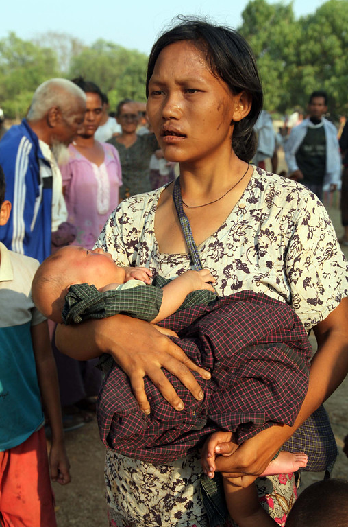 . Carrying her child a Muslim woman tries to move a rescue camp in Meikhtila  about 550 kilometers (340 miles) north of Yangon, Myanmar, Friday, March 22, 2013.  (AP Photo/Khin Maung Win)