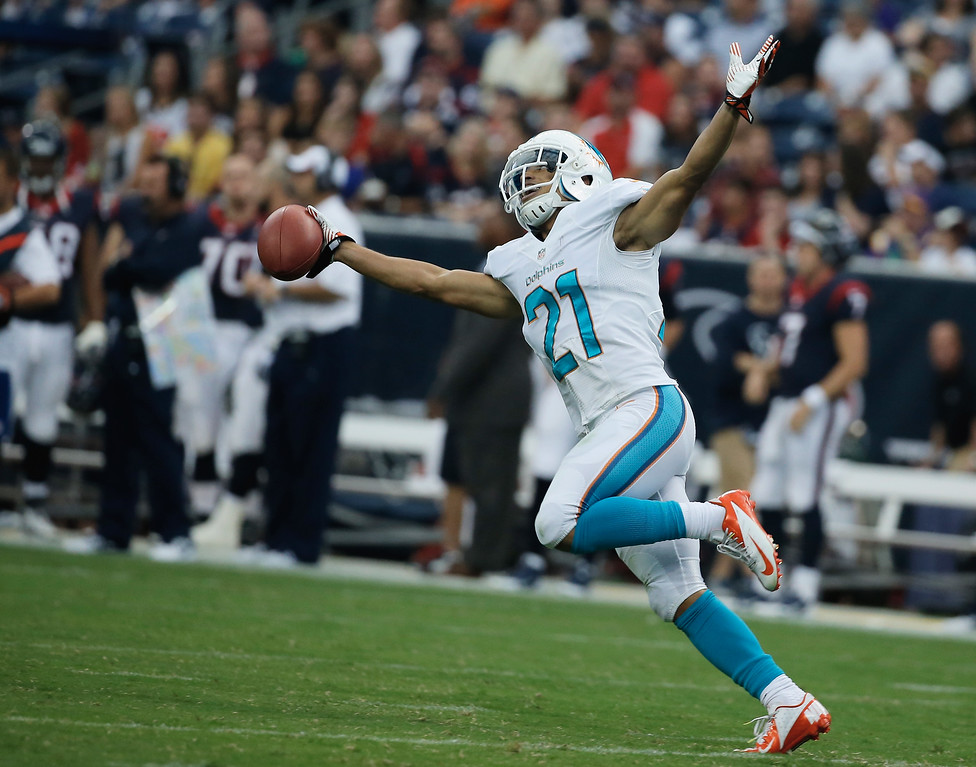 . HOUSTON, TX - AUGUST 17:  Brent Grimes #21 of the Miami Dolphins celebrates after making a first quarter interception against the Houston Texans during a preseaon game at Reliant Stadium on August 17, 2013 in Houston, Texas.  (Photo by Scott Halleran/Getty Images)