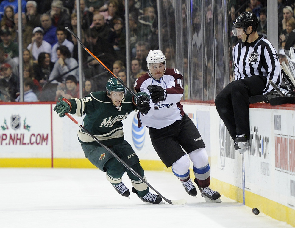. Jonas Brodin #25 of the Minnesota Wild and Brad Malone #42 of the Colorado Avalanche skate after the puck as linesman Ryan Galloway #82 gets out of the way during the first period of the game on November 29, 2013 at Xcel Energy Center in St Paul, Minnesota. The Avalanche defeated the Wild 3-1. (Photo by Hannah Foslien/Getty Images)