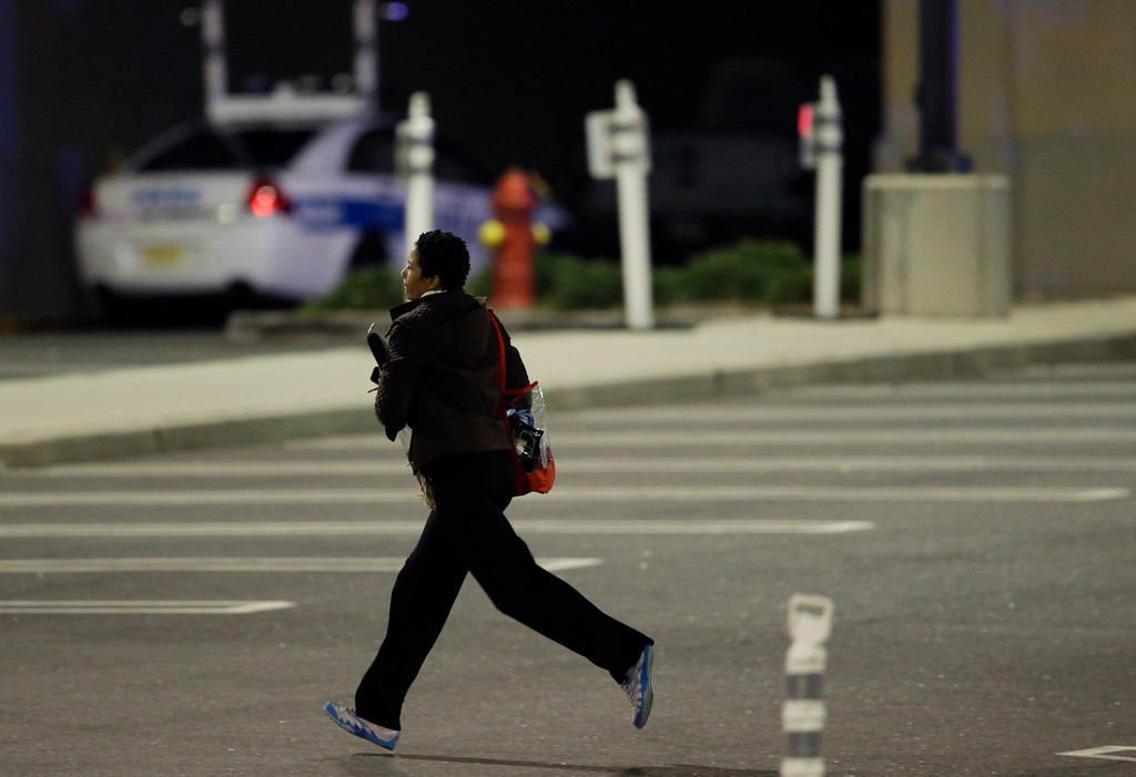 . A woman runs in the parking lot of the Garden State Plaza Mall following reports of a shooter, Monday, Nov. 4, 2013, in Paramus, N.J. Hundreds of law enforcement officers converged on the mall Monday night after witnesses said multiple shots were fired there. (AP Photo/Julio Cortez)