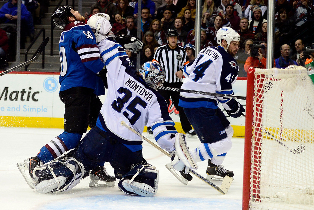 . Al Montoya (35) of the Winnipeg Jets hits Ryan O\'Reilly (90) of the Colorado Avalanche during the third period of action. The Colorado Avalanche lost 2-1 to the Winnipeg Jets at the Pepsi Center on Sunday, December 29, 2013. (Photo by AAron Ontiveroz/The Denver Post)