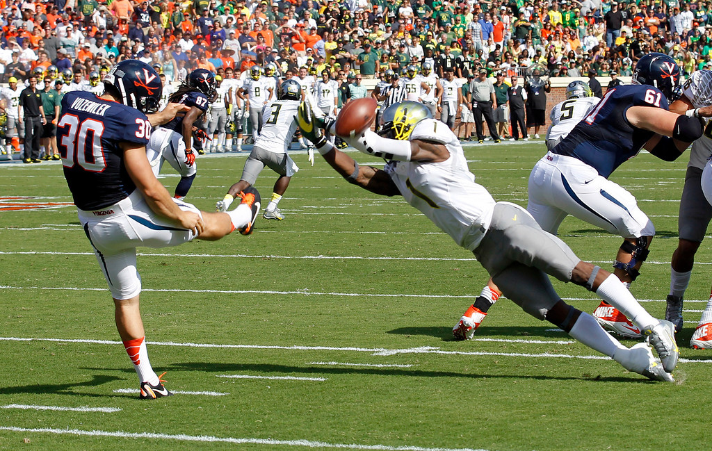 . Oregon wide receiver Josh Huff (1) tips a punt from Virginia punter Alec Vozenilek (30) during the first half of an NCAA college football game at Scott Stadium, Saturday, Sept. 7, 2013, in Charlottesville, Va. (AP Photo/Andrew Shurtleff)