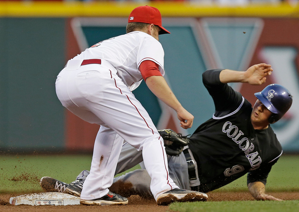 . Colorado Rockies\' DJ LeMahieu (9) steals second base as Cincinnati Reds shortstop Zack Cozart puts down the late tag in the fourth inning of a baseball game on Saturday, May 10, 2014, in Cincinnati. (AP Photo/Al Behrman)