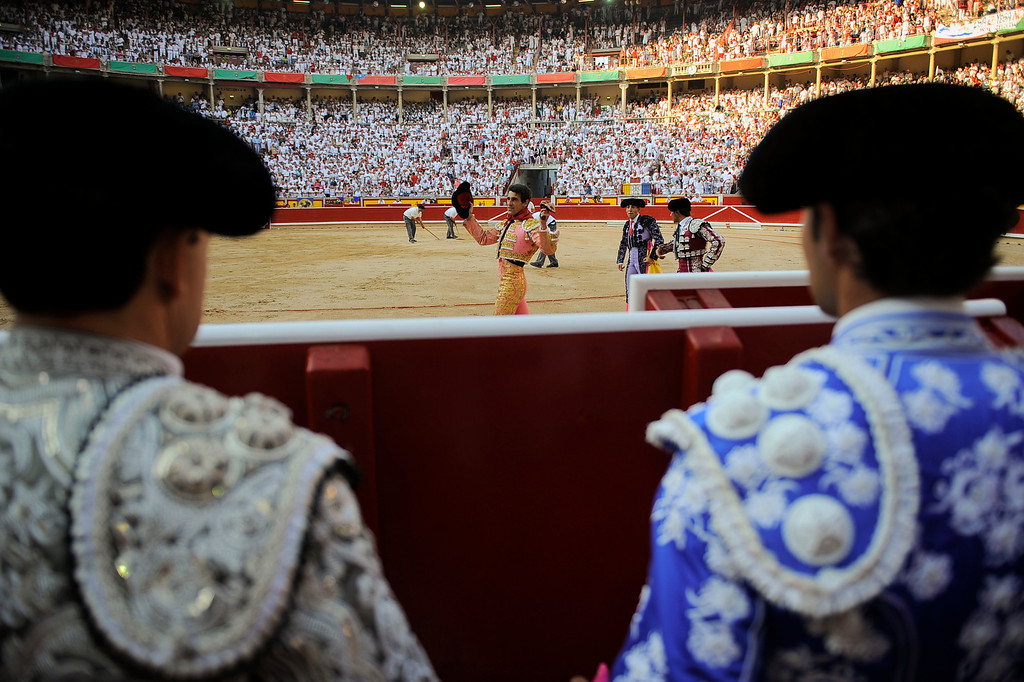. Spanish bullfighter Francisco Marco, center, is congratulated after cutting the ear of a Torrestrella\' ranch bull as his assistants watch him from the border of the bullring, at the San Fermin fiestas, in Pamplona, northern Spain on Thursday, July 11, 2013. (AP Photo/Alvaro Barrientos)