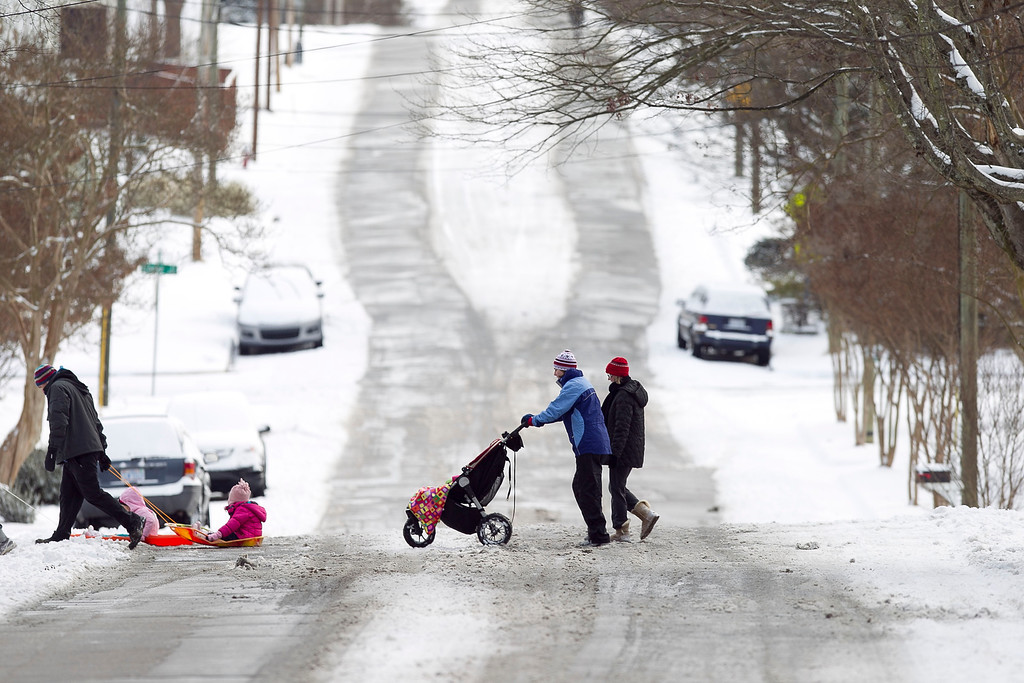 . Residents in the Historic Oakwood neighborhood cross Lane Street on Wednesday morning January 29, 2014 in Raleigh, N.C. after a winter storm dropped several inches of snow, canceling school and offering residents a chance to enjoy a winter holiday.    School systems across much of North Carolina were closed on Wednesday.  (AP Photo/The News & Observer,Robert Willet)