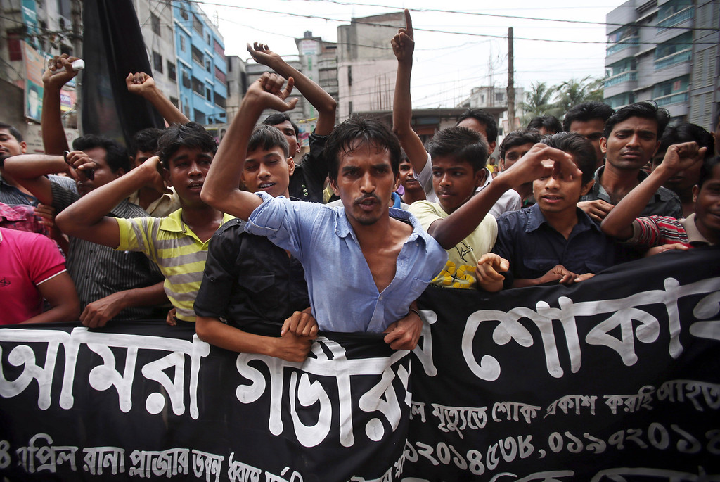 """. Workers at a garment factory just streets away from the recently collapsed garment factory building, protest as they refuse to work when they found cracks in their current office building, Tuesday, April 30, 2013 in Savar, near Dhaka, Bangladesh.   A top Bangladesh court on Tuesday ordered the government to \""""immediately\"""" confiscate the property of a collapsed building\'s owner, as thousands of protesters demanding death penalty for the man clashed with police, leaving 100 people injured. (AP Photo/Wong Maye-E)"""