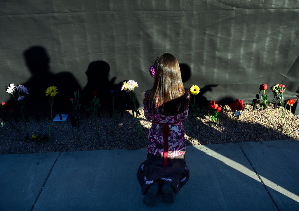 . DENVER, CO - JANUARY 18: After placing a flower, Summer Urban, 7, of Highlands Ranch, kneels and prays outside the property of Planned Parenthood of the Rocky Mountains. Denver Archbishop Samuel Aquila leads an annual prayer event on the anniversary of Roe vs. Wade. The event, 41 Year Remembrance: Honoring Denver\'s Children Lost to Abortion, began at the Lighthouse Women\'s Center in Denber with prayer and song, and ended with a procession to Planned Parenthood of the Rocky Mountains where participants placed flowers along the fence lining the property. (Photo by Kathryn Scott Osler/The Denver Post)