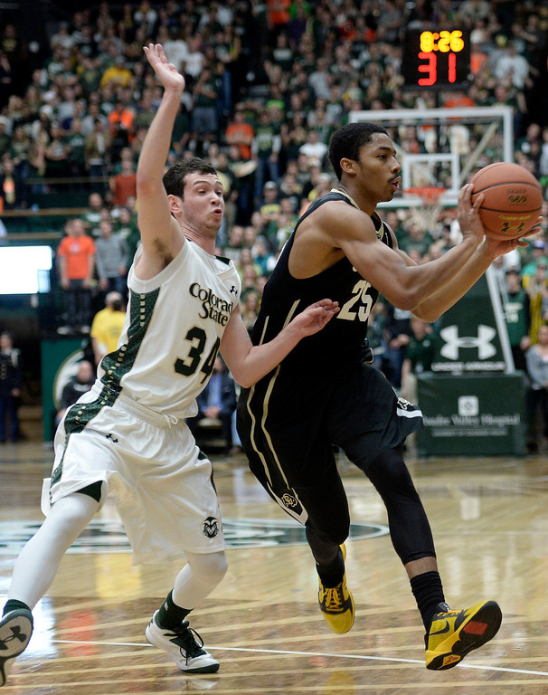 . CU\'s Spencer dinwiddie looks for an open teammate while dribbling the ball past David Cohn during an NCAA game against CSU on Tuesday, Dec. 3, 2013, at the Moby Arena in Fort Collins.
