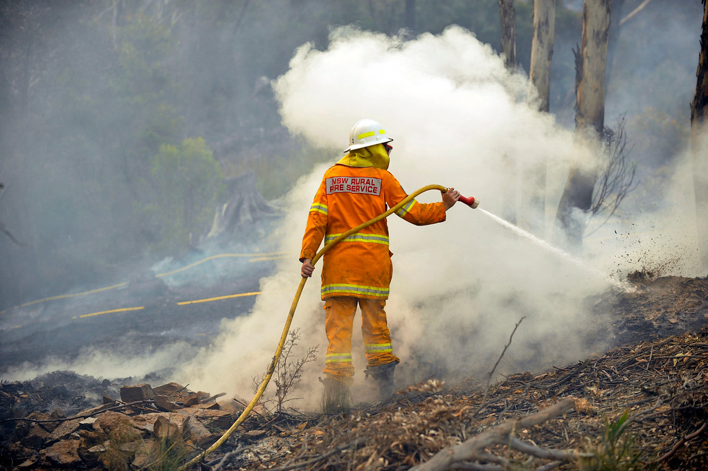 . A New South Wales Rural Fire Service volunteer puts out a spot fire in the town of Bell, Australia, on Sunday, Oct. 20, 2013.  (AP Photo/AAP Image/Paul Miller)