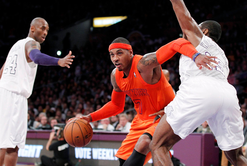 . New York Knicks\' Carmelo Anthony (C) gets called for an offensive foul as Los Angeles Lakers\' Metta World Peace (R) guards him and Kobe Bryant (L) looks on during the first half of their NBA basketball game in Los Angeles December 25, 2012. REUTERS/Danny Moloshok