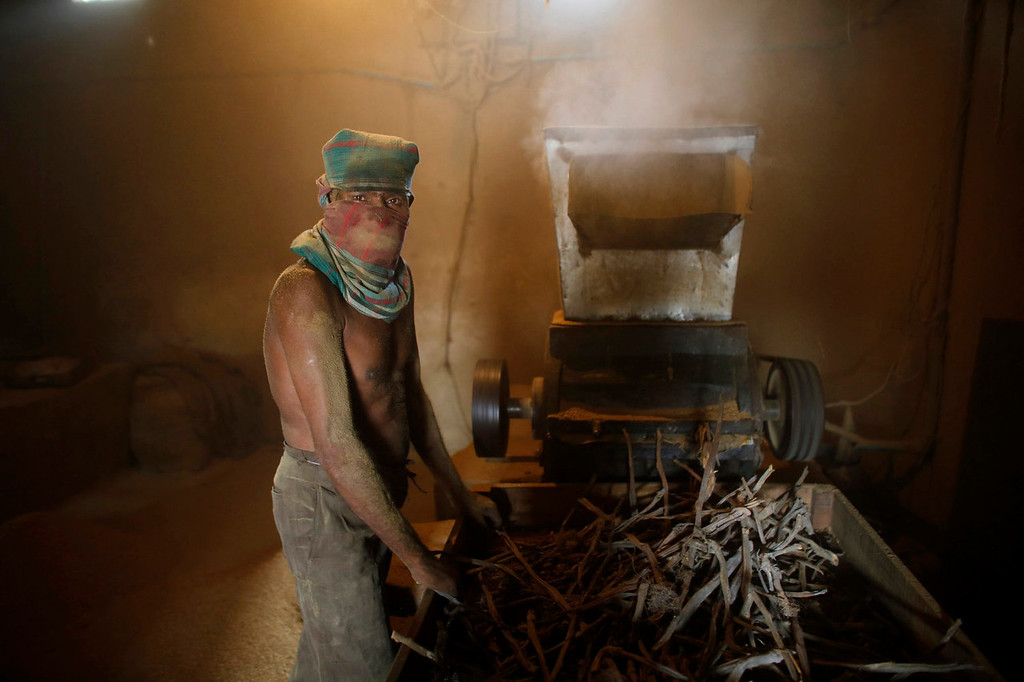 ". A worker crushes locally grown tobacco in a grinding machine in a small \'bidi\' (cigarette) factory at Haragach in Rangpur district, Bangladesh July 11, 2013. According to a 2012 study by US-based NGO, Campaign for Tobacco-Free Kids, over 45,000 people in Bangladesh are employed in manufacturing inexpensive cigarettes known as bidis and this number includes ""many women and children working in household based establishments where they make low wages and live in poverty.\"" A 2011 research paper about bidi workers in Bangladesh, published in the journal Tobacco Control, says that working conditions can involve poor ventilation and exposure to tobacco dust, which can cause a range of health problems including respiratory and skin diseases. International attention has been focused on workers\' safety in Bangladesh since the disaster at Rana Plaza, a garment factory complex which collapsed in April, killing 1,132 workers.   REUTERS/Andrew Biraj"