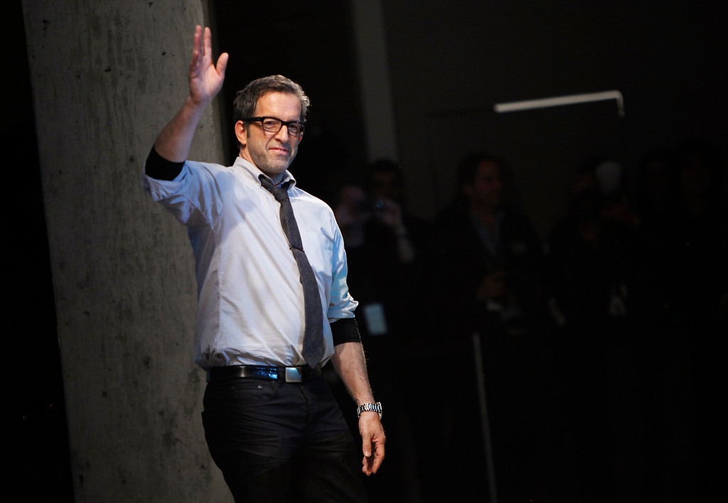 . Designer Kenneth Cole waves following the Autumn/Winter 2013 collection during New York Fashion Week in New York, February 7, 2013. REUTERS/Carlo Allegri  (