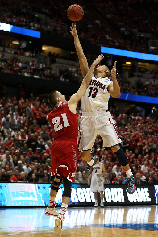 . Nick Johnson #13 of the Arizona Wildcats goes up for a shot against Josh Gasser #21 of the Wisconsin Badgers in the second half during the West Regional Final of the 2014 NCAA Men\'s Basketball Tournament at the Honda Center on March 29, 2014 in Anaheim, California.  (Photo by Jeff Gross/Getty Images)