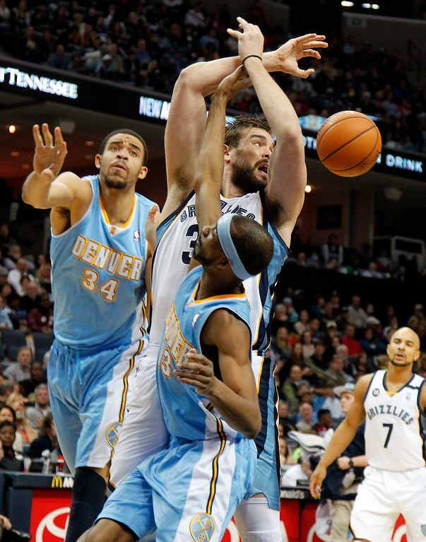 . Denver Nuggets defenders JaVale McGee (34) and Corey Brewer (13) knock the ball away from Memphis Grizzlies center Marc Gasol, center, of Spain, in the first half of an NBA basketball game on Saturday, Dec. 29, 2012, in Memphis, Tenn. (AP Photo/Lance Murphey)