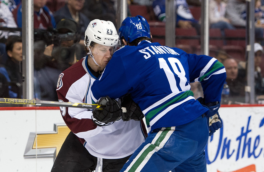 . Ryan Stanton #18 of the Vancouver Canucks collides with Nathan MacKinnon #29 of the Colorado Avalanche during the first period in NHL action on April 10, 2014 at Rogers Arena in Vancouver, British Columbia, Canada.  (Photo by Rich Lam/Getty Images)