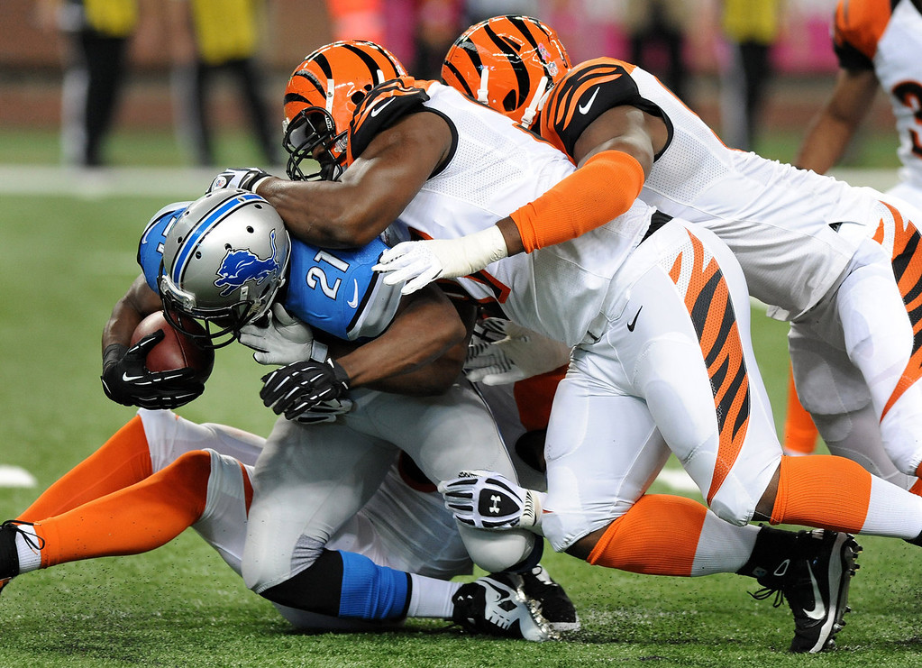 . Detroit Lions running back Reggie Bush (21) is stopped by Cincinnati Bengals defensive tackle Geno Atkins, middle and defensive end Michael Johnson, right, in the first quarter of an NFL football game against Sunday, Oct. 20, 2013, in Detroit. (AP Photo/Jose Juarez)