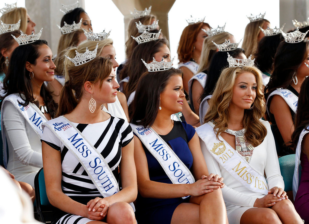 . Miss South Carolina Brooke Mosteller, front left, Miss South Dakota Tessa Dee, front center, and Miss Tennessee Shelby Thompson, front right,  listen with other Miss America contestants during introductions after arriving in Atlantic City, N.J. on Tuesday, Sept. 3, 2013. The Miss America pageant is back in the city where it began, six years after spurning the city for Las Vegas. The pageant held a welcoming ceremony Tuesday for the 53 contestants, one from each state plus the District of Columbia, Puerto Rico and the U.S. Virgin Islands. The contestants filed out of Boardwalk Hall, where the competition will begin next week and culminate days later, and walked across the Boardwalk to a stage. (AP Photo/Mel Evans)