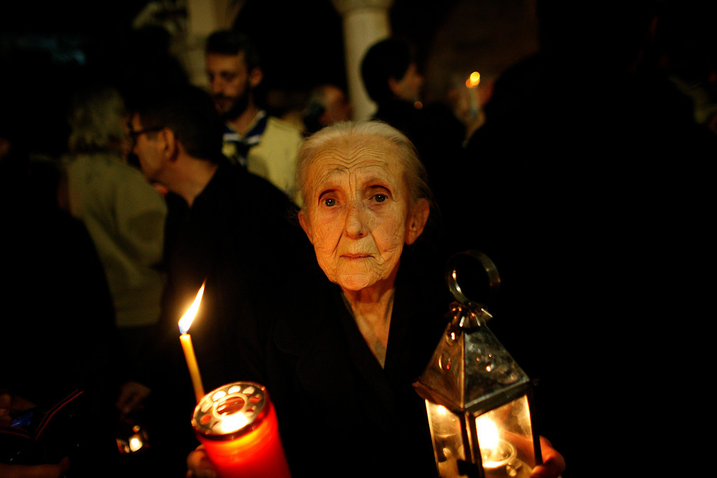 . An elderly  woman carries the Holy Fire during an Easter Mass at the church of Agii Anargyri in Athens, late Saturday, April 19, 2014. The Holy Fire is brought in Greece every year from the church of the Holy Sepulcher in Jerusalem, traditionally believed to be the burial site of Jesus Christ . (AP Photo/Kostas Tsironis)