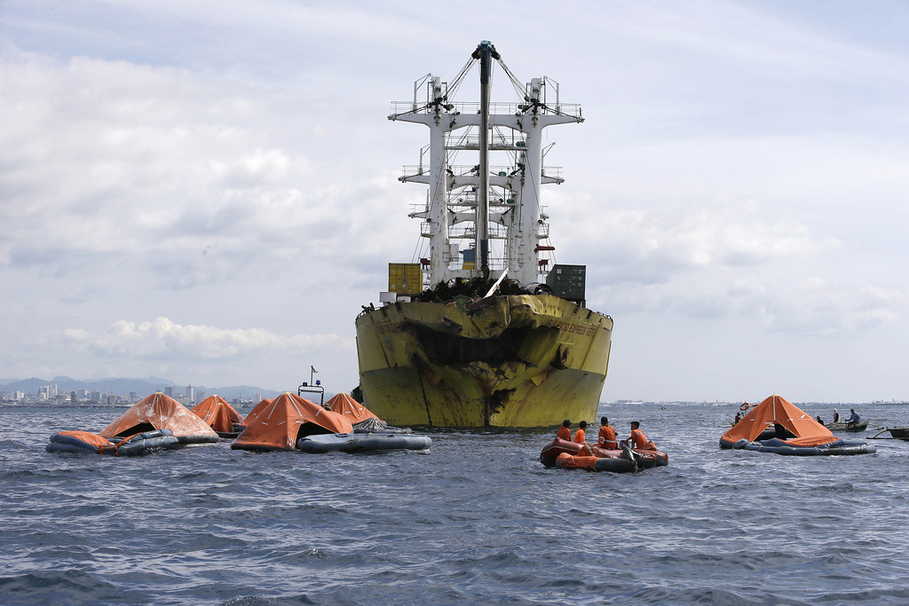 . A cluster of life rafts floate near the cargo ship Sulpicio Express Siete with its damaged bow a day after it collided with a passenger ferry off the waters of Talisay city, Cebu province in central Philippines, Saturday Aug. 17, 2013. Divers combed through a sunken ferry Saturday to retrieve the bodies of more than 200 people still missing from an overnight collision with a cargo vessel near the central Philippine port of Cebu that sent passengers jumping into the ocean and leaving many others trapped. At least 28 were confirmed dead and hundreds rescued. The captain of the ferry MV Thomas Aquinas, which was approaching the port late Friday, ordered the ship abandoned when it began listing and then sank just minutes after collision with the MV Sulpicio Express, coast guard deputy chief Rear Adm. Luis Tuason said. (AP Photo/Bullit Marquez)