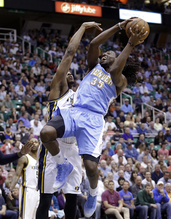 . Denver Nuggets\' Kenneth Faried (35) goes to the basket as Utah Jazz\'s Derrick Favors, rear, defends in the first quarter during an NBA basketball game on Wednesday, April 3, 2013, in Salt Lake City. (AP Photo/Rick Bowmer)