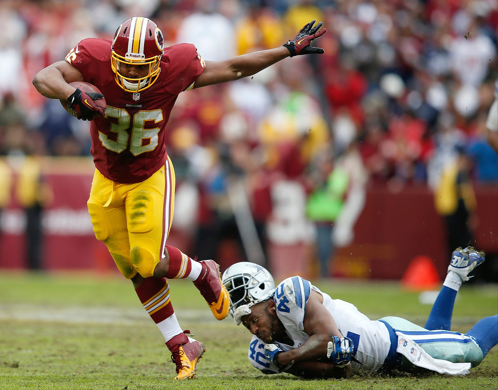 . Washington Redskins fullback Darrel Young knocks the helmet off of Dallas Cowboys free safety Barry Church during the second half of an NFL football game in Landover, Md., Sunday, Dec. 22, 2013. (AP Photo/Evan Vucci)