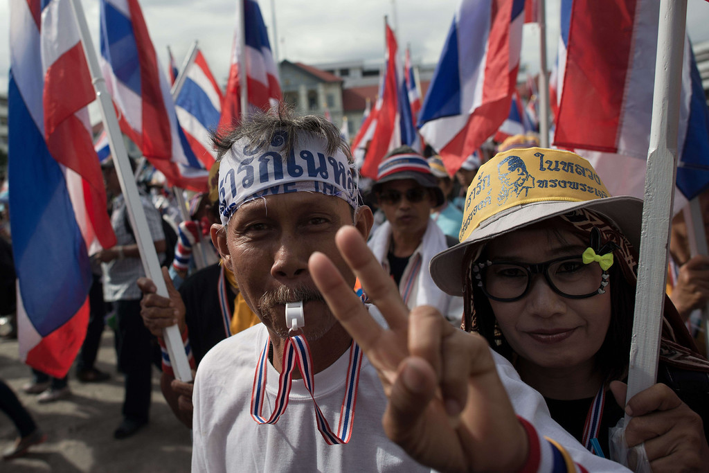 . Anti-government protestors wave flags as they parade inside the Thai army headquarters during a protest in Bangkok on November 29, 2013.  AFP PHOTO/ Nicolas  ASFOURI/AFP/Getty Images