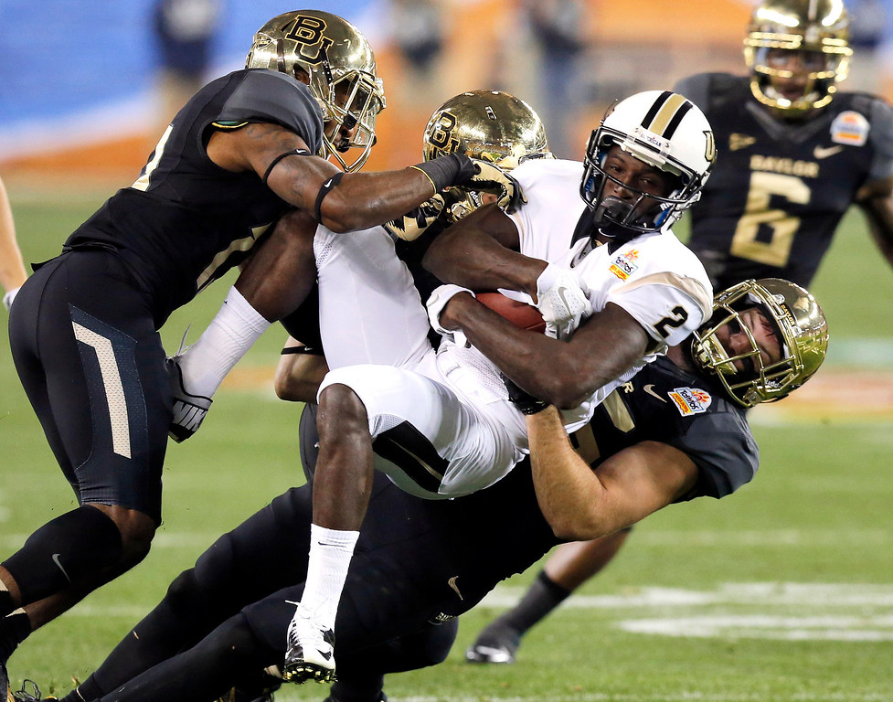 . Central Florida wide receiver Jeff Godfrey (2) is tackled by, from left, Baylor\'s Terrell Burt, Eddie Lackey and Sam Holl during the first half of the Fiesta Bowl NCAA college football game, Wednesday, Jan. 1, 2014, in Glendale, Ariz  (AP Photo/Ross D. Franklin)
