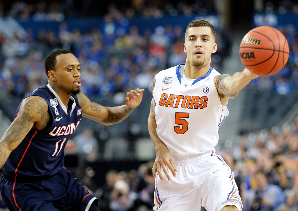 . Florida guard Scottie Wilbekin (5) passes as Connecticut guard Ryan Boatright (11) defends during the first half of the NCAA Final Four tournament college basketball semifinal game Saturday, April 5, 2014, in Arlington, Texas. (AP Photo/Eric Gay)