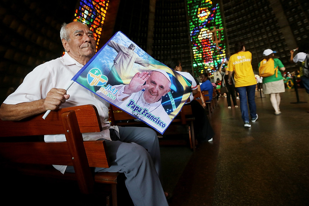 . A man holds a Pope Francis flag inside the Metropolitan Cathedral before the arrival of Pope Francis on July 22, 2013 in Rio de Janeiro, Brazil. (Photo by Mario Tama/Getty Images)