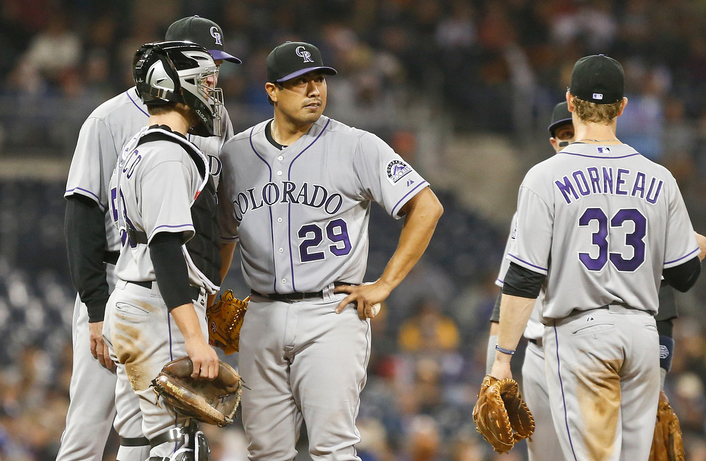 . Colorado Rockies starting pitcher Jorge De La Rosa, center, gets a visit from catcher Jordan Pacheco and pitching coach Jim Wright in the fifth inning of a baseball game Wednesday, April 16, 2014, in San Diego.  (AP Photo/Lenny Ignelzi)
