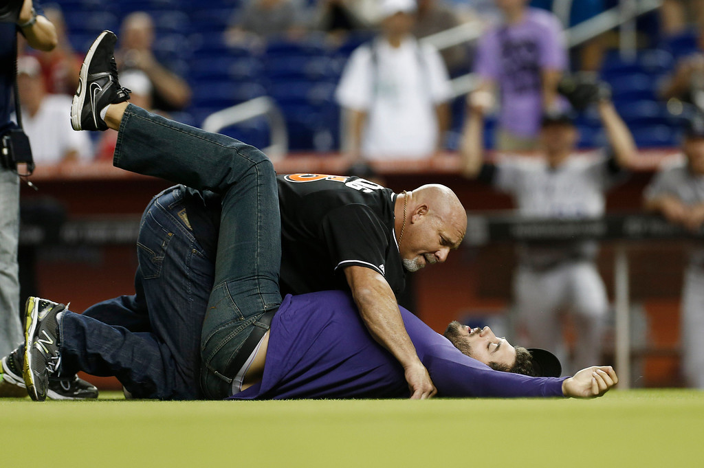 ". Professional wrestler Bill Goldberg, left, tackles a ""bad guy\"" on the field before a baseball game in Miami between the Colorado Rockies and Miami Marlins, Saturday, Aug. 24, 2013. (AP Photo/J Pat Carter)"