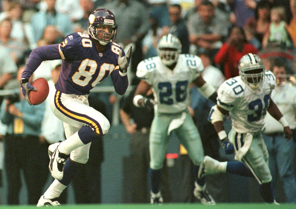 . IRVING, UNITED STATES:  Cris Carter of the Minnesota Vikings (80) runs away from Dallas Cowboys defenders Darren Woodson (28) and Kenny Wheaton (30) en route to a 54 yard touchdown reception during the first quarter of action at Texas Stadium in Irving, TX, 26 November.   PAUL BUCK/AFP/Getty Images