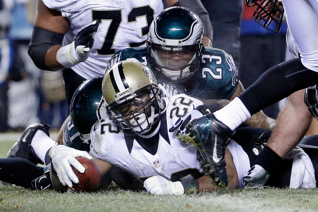 . New Orleans Saints\' Mark Ingram (22) scores a touchdown as Philadelphia Eagles\' Patrick Chung (23) defends during the second half of an NFL wild-card playoff football game, Saturday, Jan. 4, 2014, in Philadelphia. (AP Photo/Matt Rourke)