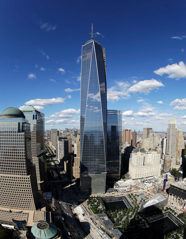 . In this Thursday, Sept. 5, 2013, file photo taken with a fisheye lens, 1 World Trade Center, center, overlooks the wedge-shaped pavilion entrance of the National September 11 Museum, lower right, and the square outlines of the memorial waterfalls  in New York. According to the nonprofit Council on Tall Buildings and Urban Habitat, 1 World Trade Center, once completed, will be the third tallest building in the world with a height of 1,776 feet. (AP Photo/Mark Lennihan, File)