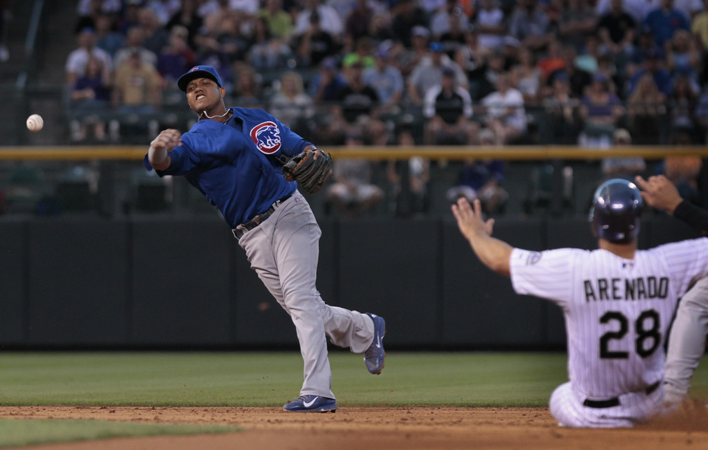 . Chicago Cubs shortstop Starlin Castro (13) throws to first base to force out Colorado Rockies\' Justin Morneau as Rockies\' Nolan Arenado (28) slides into second base to end the fifth inning of a baseball game in Denver on Tuesday, Aug. 5, 2014.(AP Photo/Joe Mahoney)