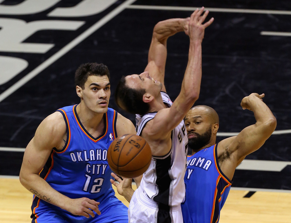. Steven Adams #12 and Derek Fisher #6 of the Oklahoma City Thunder defend Manu Ginobili #20 of the San Antonio Spurs in the first half during Game Five of the Western Conference Finals of the 2014 NBA Playoffs at AT&T Center on May 29, 2014 in San Antonio, Texas.   (Photo by Chris Covatta/Getty Images)