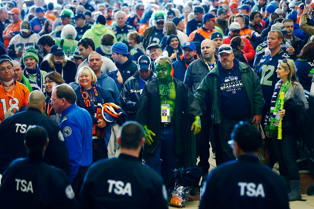 . Football fans wait to go through security at the Secaucus Junction, Sunday, Feb. 2, 2014, in Secaucus, N.J. The Seattle Seahawks are scheduled to play the Denver Broncos in the NFL Super Bowl XLVIII football game on Sunday, evening at MetLife Stadium in East Rutherford, N.J. (AP Photo/Matt Rourke)