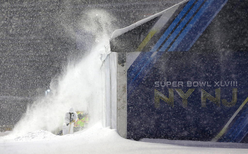 . Workers shovel snow near a tent which will be used as an access point into Super Bowl XLVIII as crews prepare MetLife Stadium during a snow storm, Tuesday, Jan. 21, 2014, in East Rutherford, N.J. (AP Photo/Julio Cortez)